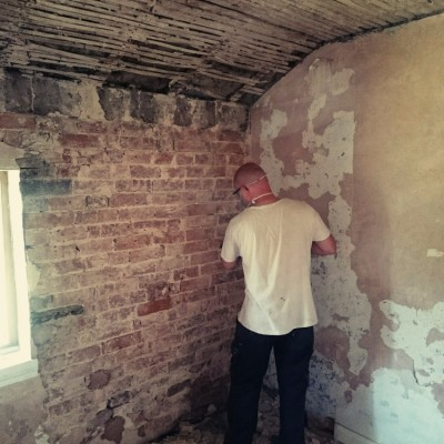 Lee hard at work preparing the walls and ceiling for fresh lime plaster finishes.